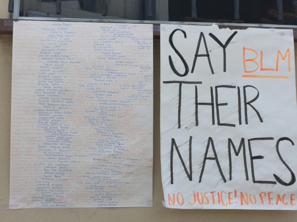 "Posters listing the names of unarmed Black folks killed at the hands of the police with the slogans ""Say Their Names,"" ""BLM,"" and ""No Justice! No Peace!"""